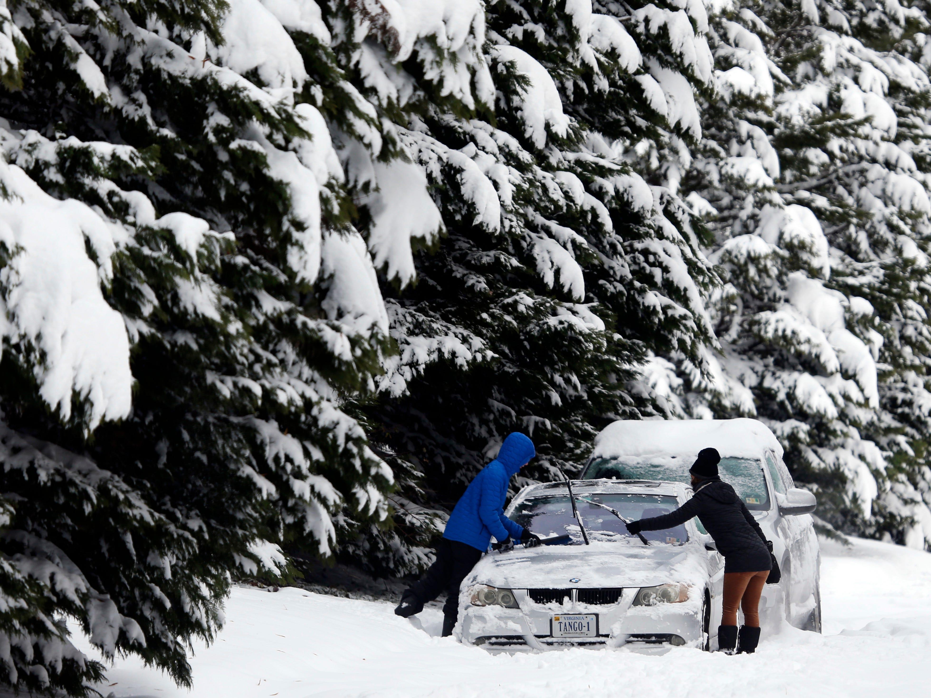 A motorist cleans snow off cars in Richmond, Va., Monday, Dec. 10, 2018.