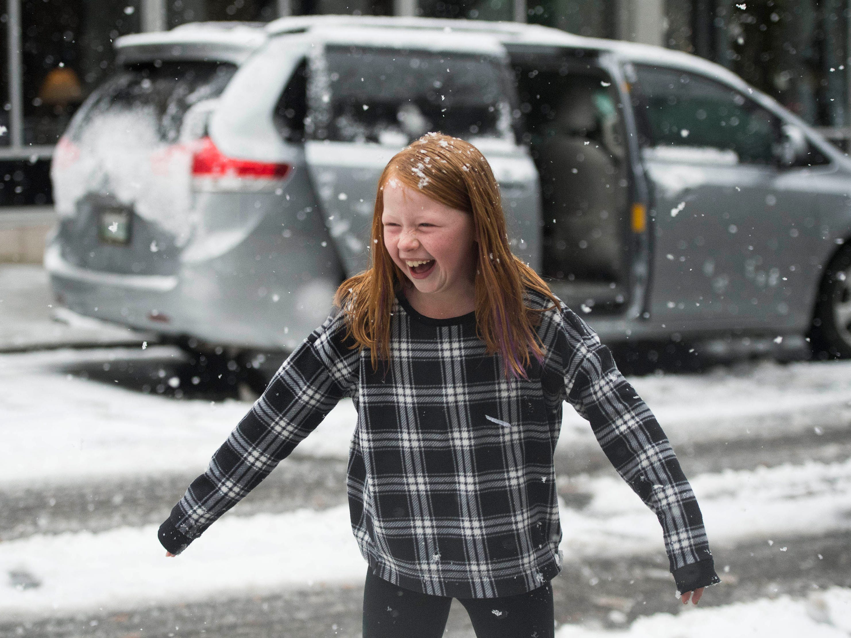 Emilia Eveland laughs during a snow fight between her brothers and dad in Downtown Knoxville, Tenn. on Dec. 9.