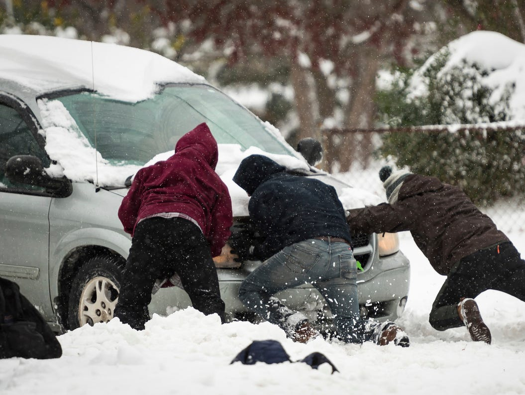 Good samaritans help a driver who is lodged in the snow, Sunday, along South Hawthorne Road in Winston-Salem, N.C.