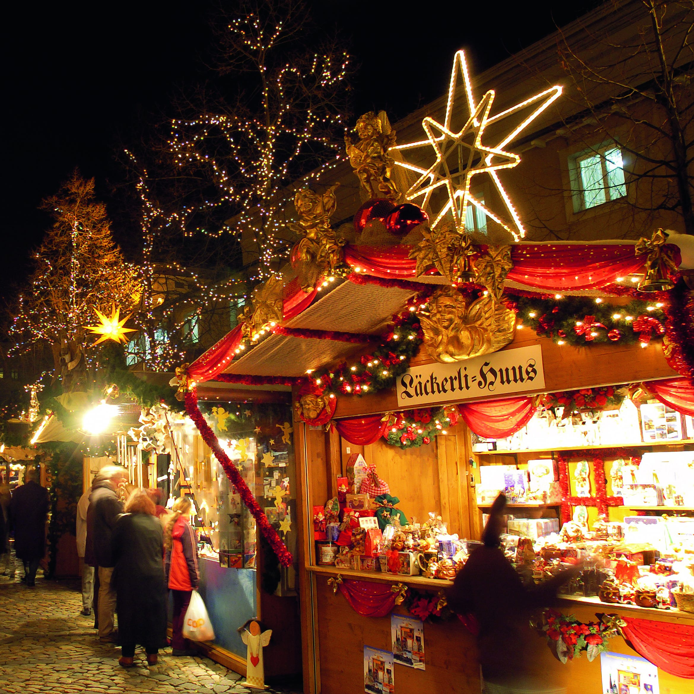 Christmas lights glow over the stalls at the Barfüsserplatz market.
