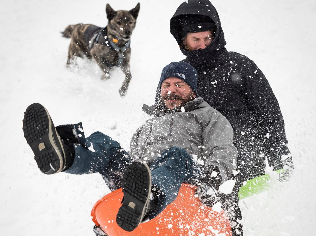 Zac Evans, front, and Stephen LaFleur go airborn sledding off a ramp while Deac, the dog, follows them down the hill at Ardmore Park Soccer Field on Sunday, in Winston-Salem, N.C.