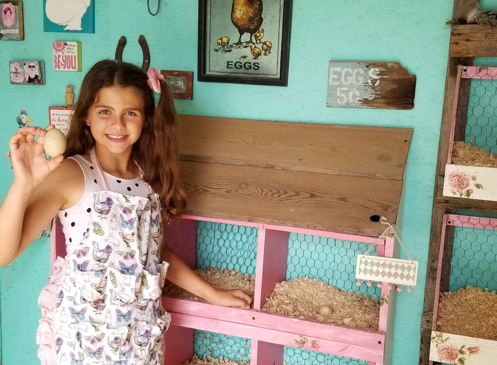 "Giselle Raad, 11, collects eggs from ""The Breakfast Club"" chicken coop on her family's property in Michigan. The coop features painted and hand-stenciled walls, art work and vintage decor including a chandelier and a painted shelf."