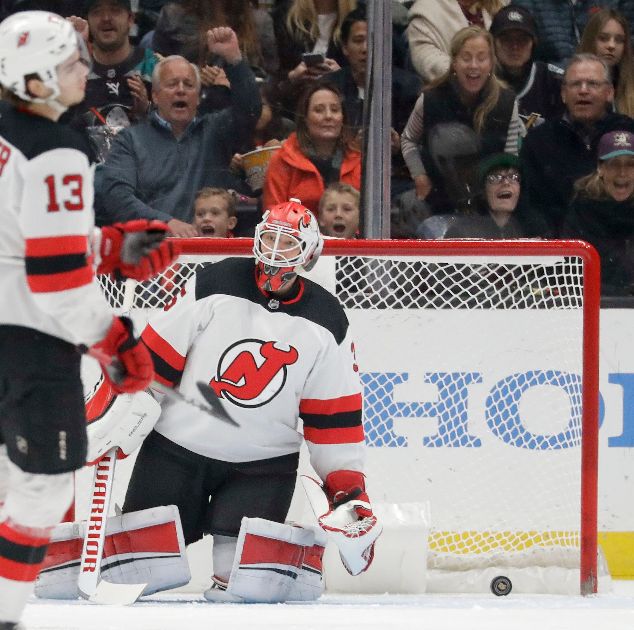 New Jersey Devils goaltender Cory Schneider and Nico Hischier react after a goal by Anaheim Ducks right wing Jakob Silfverberg during the first period.