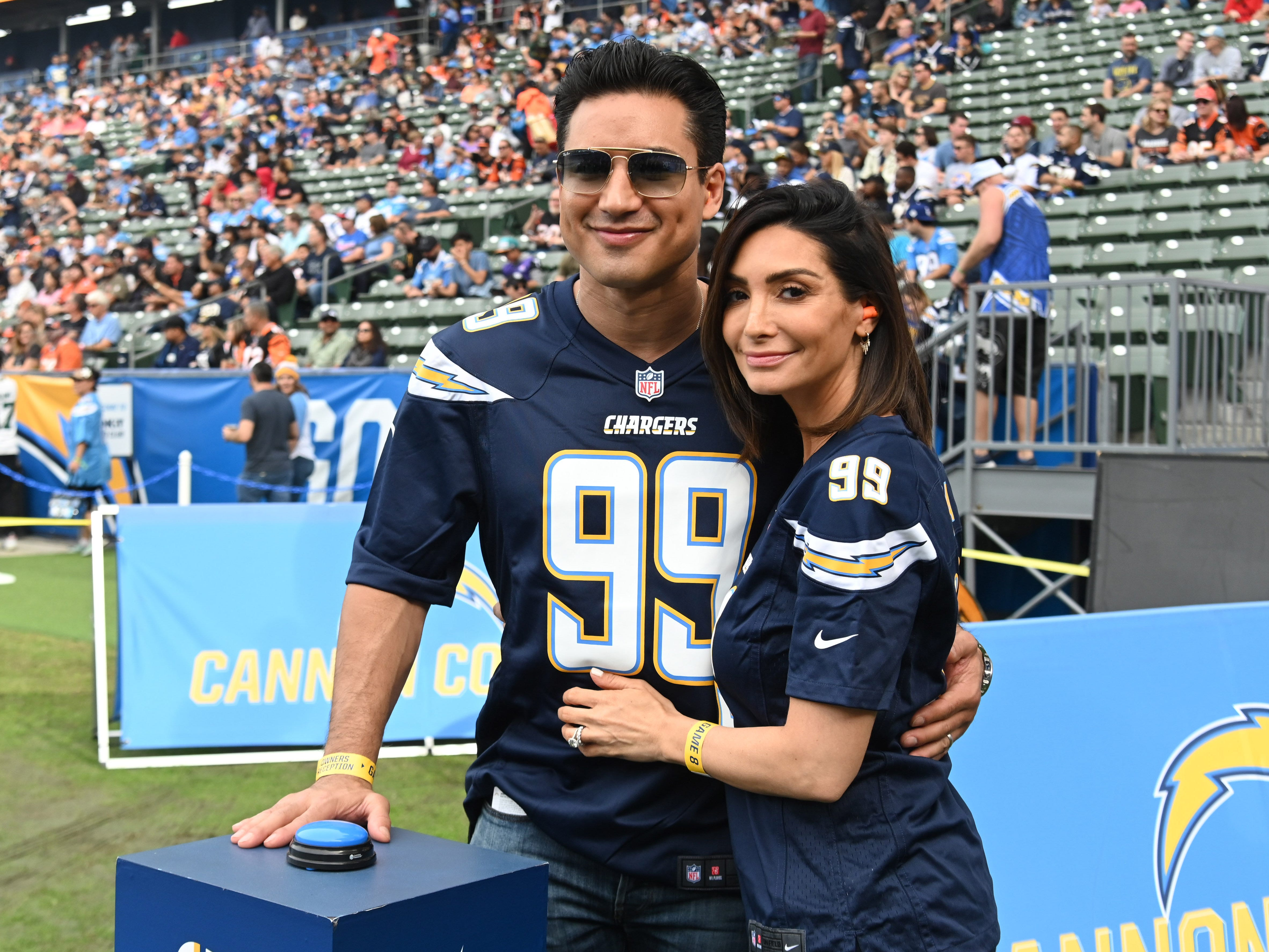Television personality Mario Lopez and wife Courtney Lopez pose during the game between the Cincinnati Bengals and the Los Angeles Chargers at StubHub Center.