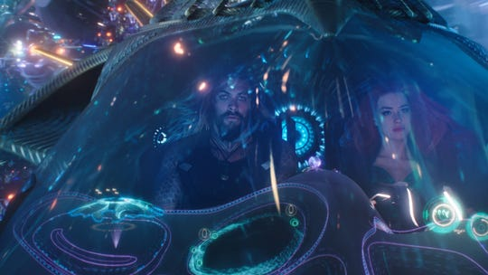 "Mera (Amber Heard) introduces Arthur (Jason Momoa) to the neon wonders of Atlantis in ""Aquaman."""