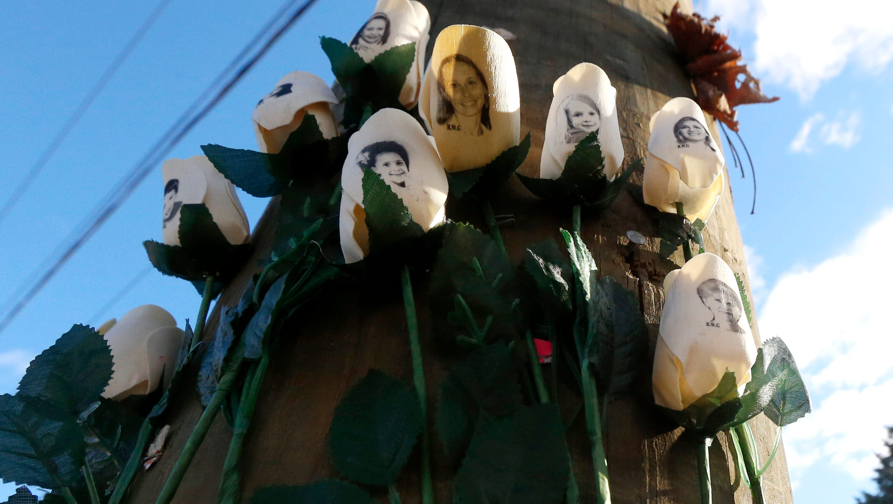 Roses with photos of shooting victims are posted on a light post at a makeshift memorial near the main intersection of the Sandy Hook village of Newtown, Conn., as the town continues to cope in the aftermath of the Sandy Hook Elementary School shooting, Wednesday, Dec. 19, 2012.