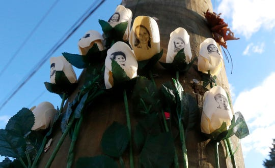 Roses with photos of shooting victims are posted on a light post at a makeshift memorial near the main intersection of the Sandy Hook village of Newtown, Conn., in the aftermath of an elementary school shooting in 2012.