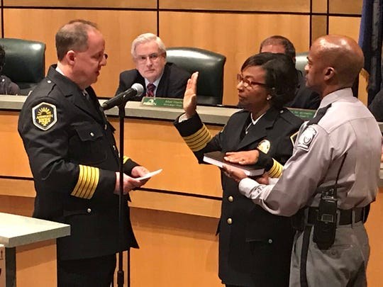 Anderson Police Chief Jim Stewart, left, administers the oath of office to Assistant Police Chief Nikki Carson on Monday night as her husband Michael holds a Bible.