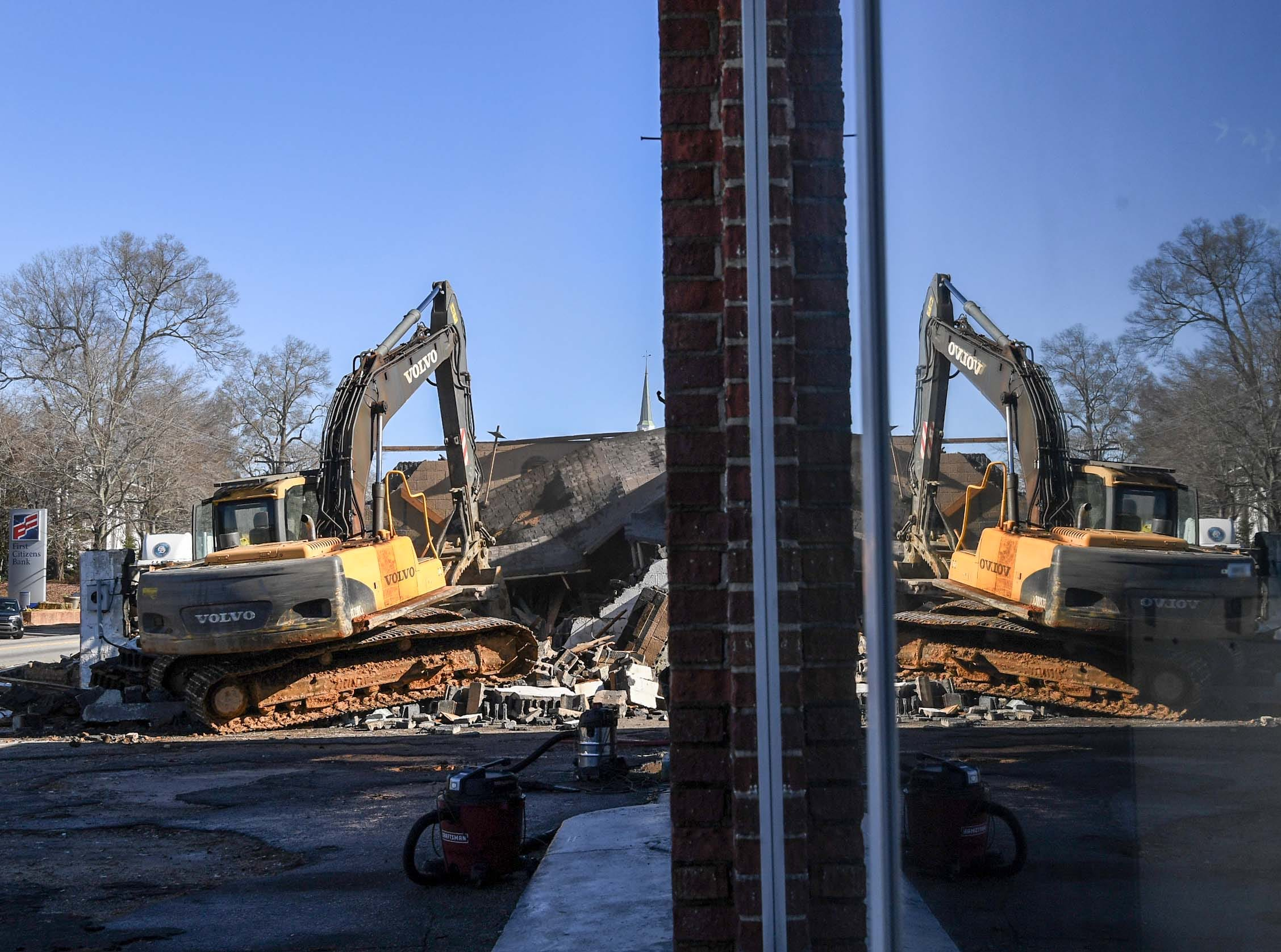 Hack Hammond of Pelzer, also in a reflection in a window at Mustang's Auto Detail, demolishes the Williamston Theater in Williamston on Tuesday.