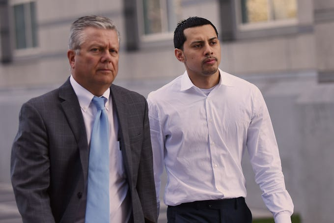 Paterson City police officer Ruben McAusland (right) appears at court in Newark after he is arrested on drug dealing charges on Friday April 20, 2018.