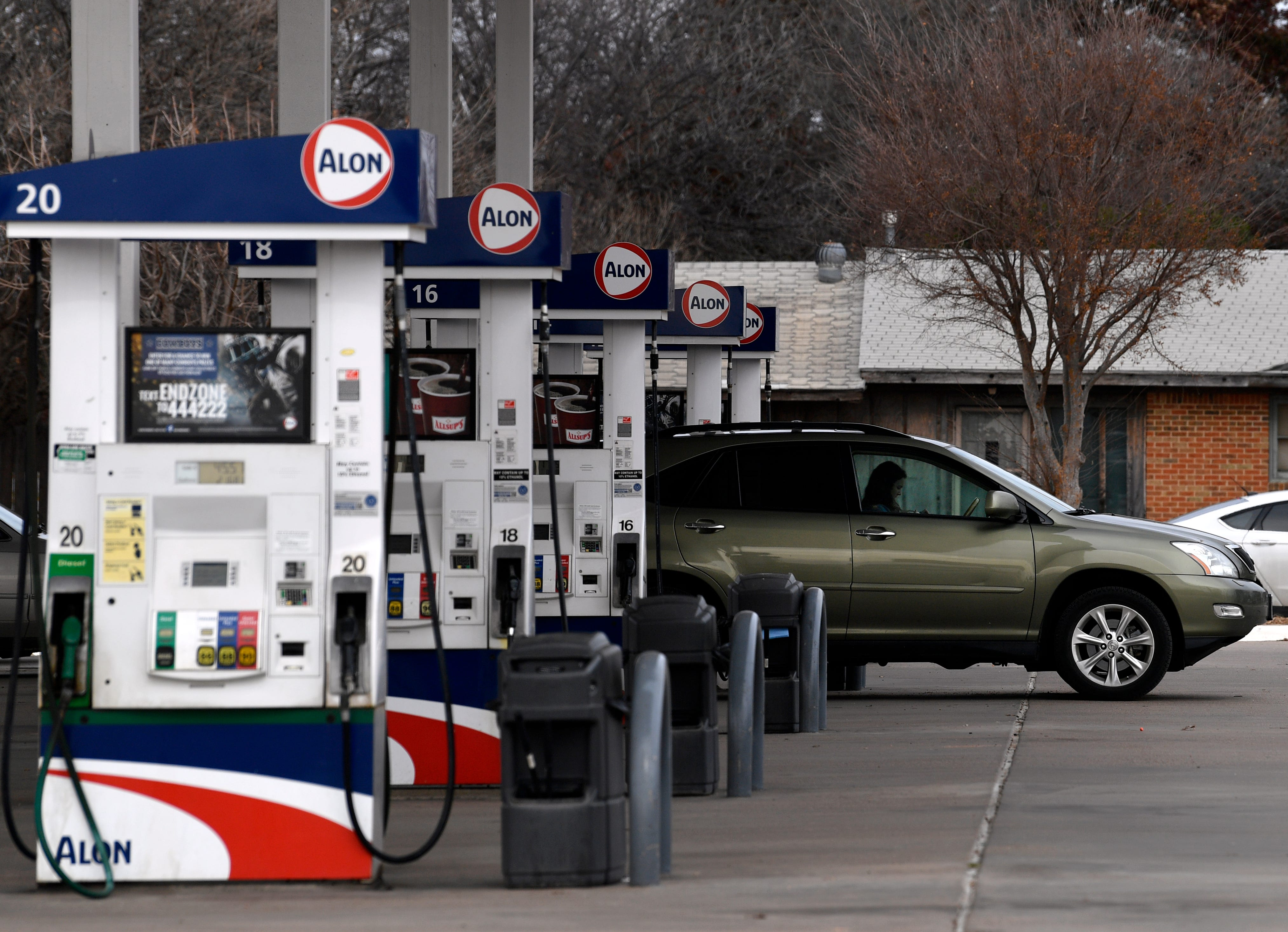 A motorist sits in car at the pump while refueling at a south Abilene gas station Tuesday.