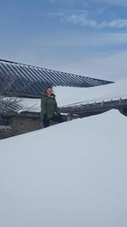 Mount Mitchell State Park seasonal office assistant Shelby Longgrear stands on top of a 6-foot snowdrift at the park restaurant on Dec. 11, 2018.