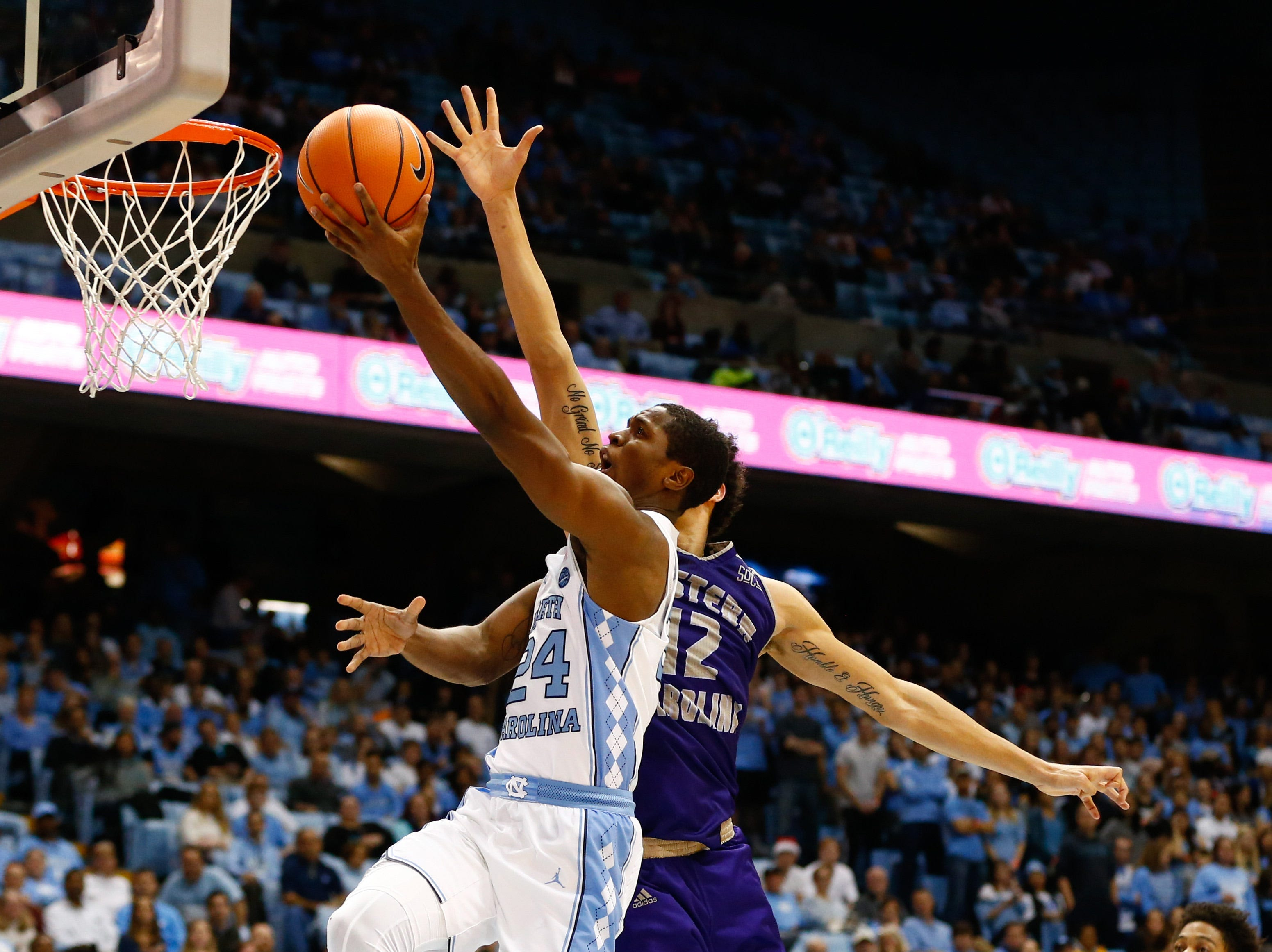 Dec 6, 2017; Chapel Hill, NC, USA; North Carolina Tar Heels guard Kenny Williams (24) goes up for a shot against Western Carolina Catamounts forward Marc Gosselin (12) in the second half at Dean E. Smith Center. Mandatory Credit: Jeremy Brevard-USA TODAY Sports