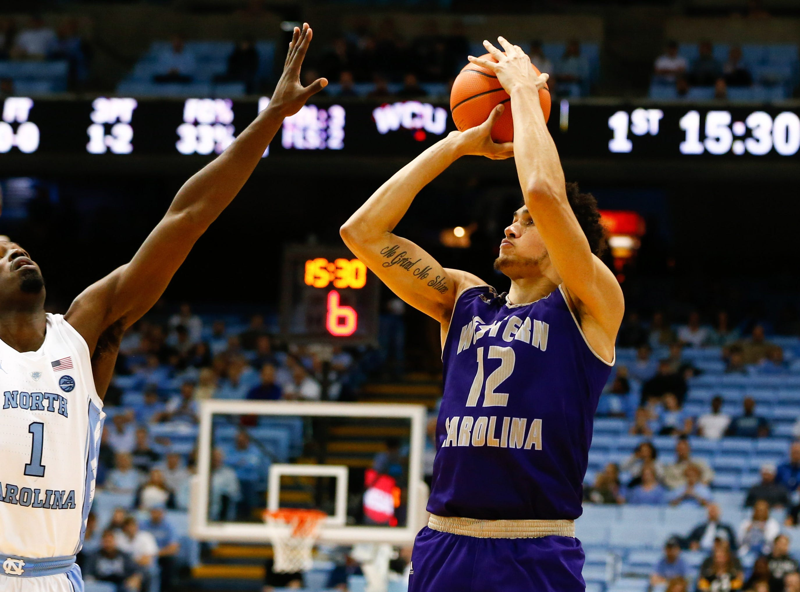 Dec 6, 2017; Chapel Hill, NC, USA; Western Carolina Catamounts forward Marc Gosselin (12) shoots the ball against North Carolina Tar Heels forward Theo Pinson (1) in the first half at Dean E. Smith Center. Mandatory Credit: Jeremy Brevard-USA TODAY Sports