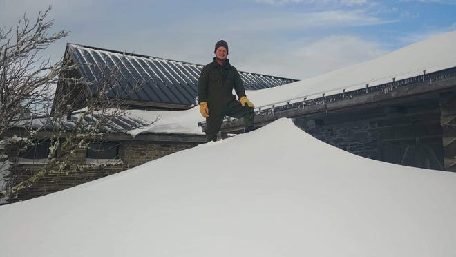 Mount Mitchell seasonal park technician Kevin Cox stands on top of a snow drift several feet high outside the park restaurant on Dec. 11, 2018.