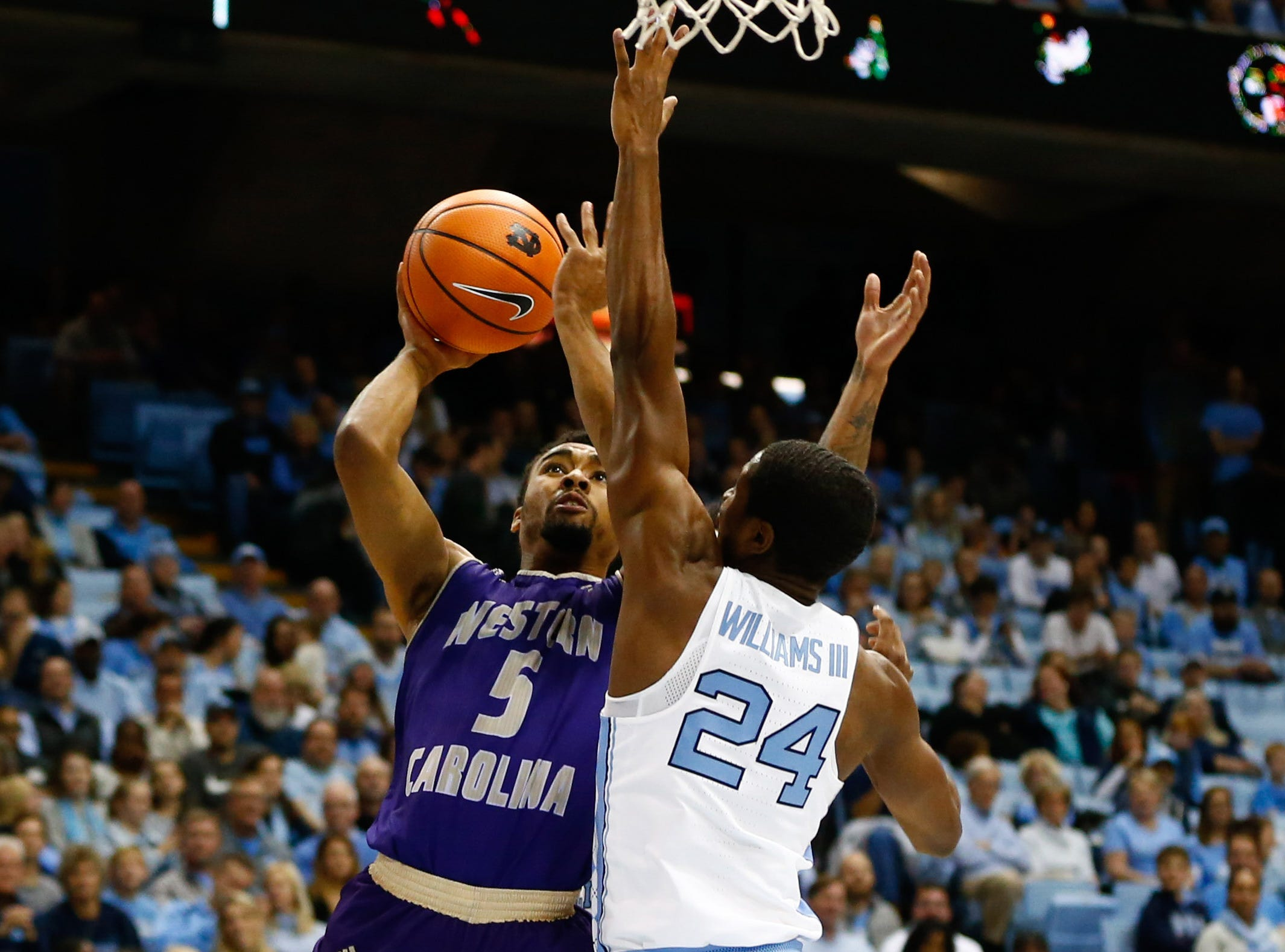 Dec 6, 2017; Chapel Hill, NC, USA; Western Carolina Catamounts guard Devin Peterson (5) shoots the ball against North Carolina Tar Heels guard Kenny Williams (24) in the first half at Dean E. Smith Center. Mandatory Credit: Jeremy Brevard-USA TODAY Sports