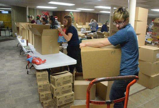 Todd VanDorsten loads a filled box onto a handcart.