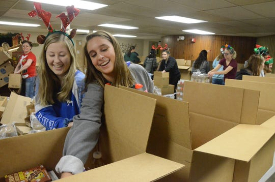 Brooke Behrndt, left, 17, and Maddie Deal, 16, from the Calhoun Area Career Center, load boxes Tuesday.