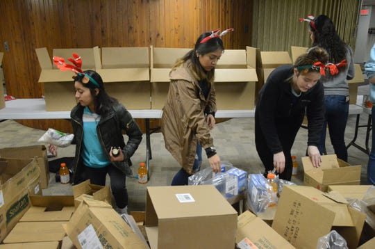 Arlene Valencia, from left, Emily Moctezuma, and Jasmine Cain, all 17, select items for Christmas baskets.