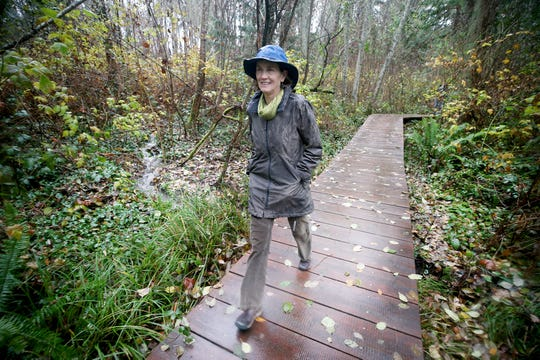 Barb Trafton, of the Bainbridge Island Parks Foundation, walks on one of the new boardwalks at Hawley Cove Park on Bainbridge Island on  Tuesday.