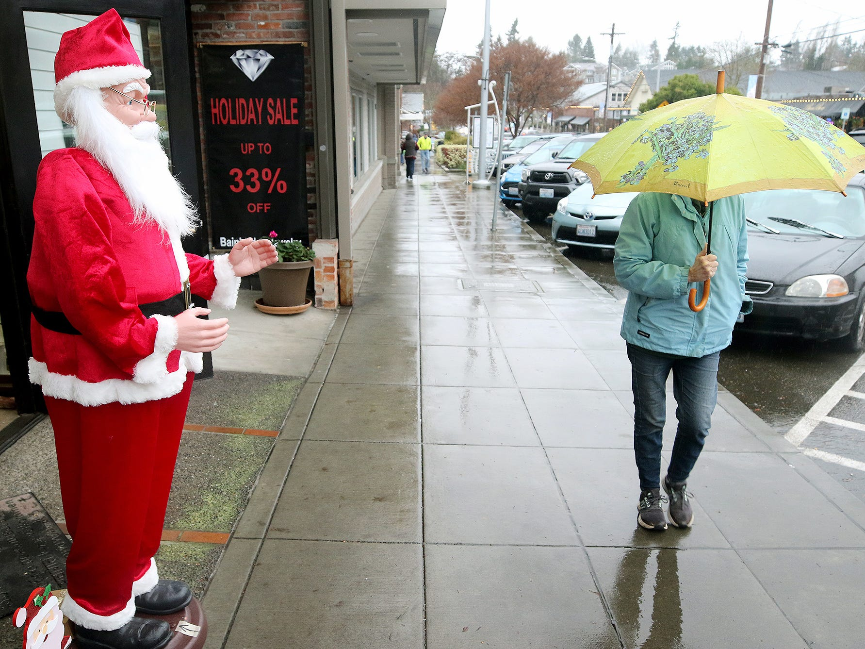 It was a wet and rainy downtown Winslow as Santa greets visitors outside of the Bainbridge Diamonds and Jewelry store on Tuesday, Dec, 11, 2018.