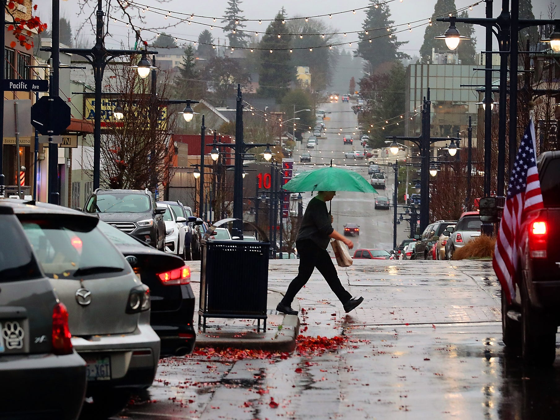 An umbrella toting pedestrian crosses 4th street while hurrying down Bremerton's Pacific Ave. in the rain on Tuesday, December 11, 2018.