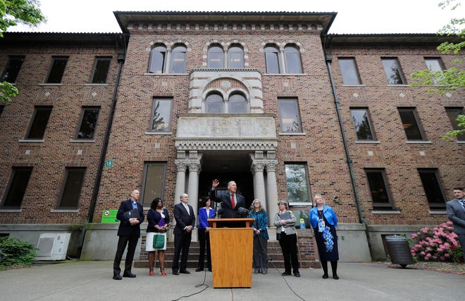 Gov. Jay Inslee, center, speaks in front of Western State Hospital in Lakewood in May. On Tuesday, Inslee unveiled his plan for fixing the state's struggling mental health system in the coming years. Inslee said he wanted to invest in the troubled Western State Hospital to address safety concerns there, but he didn't mention the rise in assaults at the state's largest psychiatric hospital.
