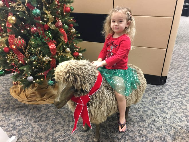 Isabella rides one of FLORIDA TODAY's vintage sheep during a recent visit to the newsroom.