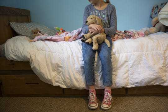 A nine-year-old girl sits in a bedroom she's making her own at St. Joseph's Orphanage emergency shelter in Anderson Township. She hugs her stuffed dog, Stinky. She's had him since she was two. She said his neck is getting floppy because of the lack of stuffing. The emergency shelter opened in January for children removed from home by Children Services. The children are closely supervised while playing and completing school lessons.