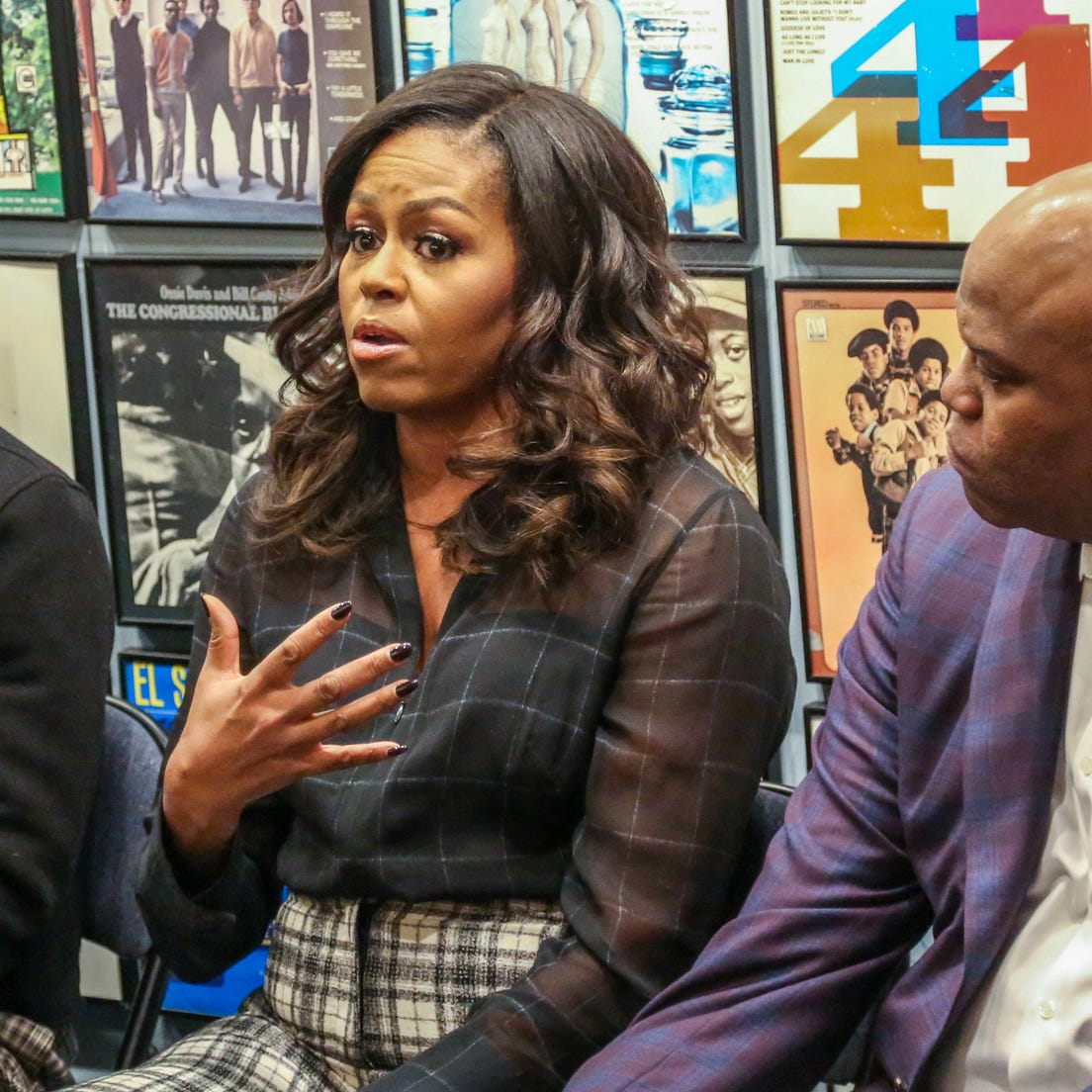 Former First Lady Michelle Obama, center, speaks about her experiences going to Princeton University alongside her brother Craig Robinson with young black men from Wayne State University at the Motown Museum in Detroit on Tuesday, Dec. 11, 2018.