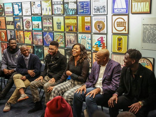 Former First Lady Michelle Obama, center, laughs with young black men from Wayne State University about her experiences going to Princeton University alongside her brother Craig Robinson, right, at Motown Museum in Detroit on Tuesday, Dec. 11, 2018.