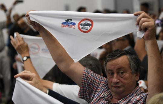 "Family members of ex-Ford Motor Co. employees hold up handkerchiefs that are stamped with a message that reads in Spanish: ""Ford never more"" in a courtroom where former Ford Motor Co. executives, who are charged with crimes against humanity for allegedly targeting Argentine union workers for kidnapping and torture after the country's 1976 military coup, await sentencing in Buenos Aires, Argentina, Tuesday, Dec. 11, 2018."