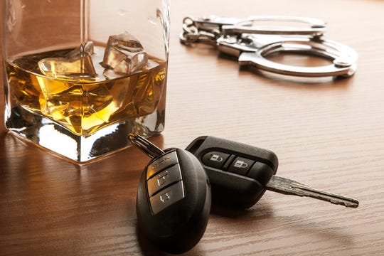 Glass of Whiskey with car keys and handcuffs