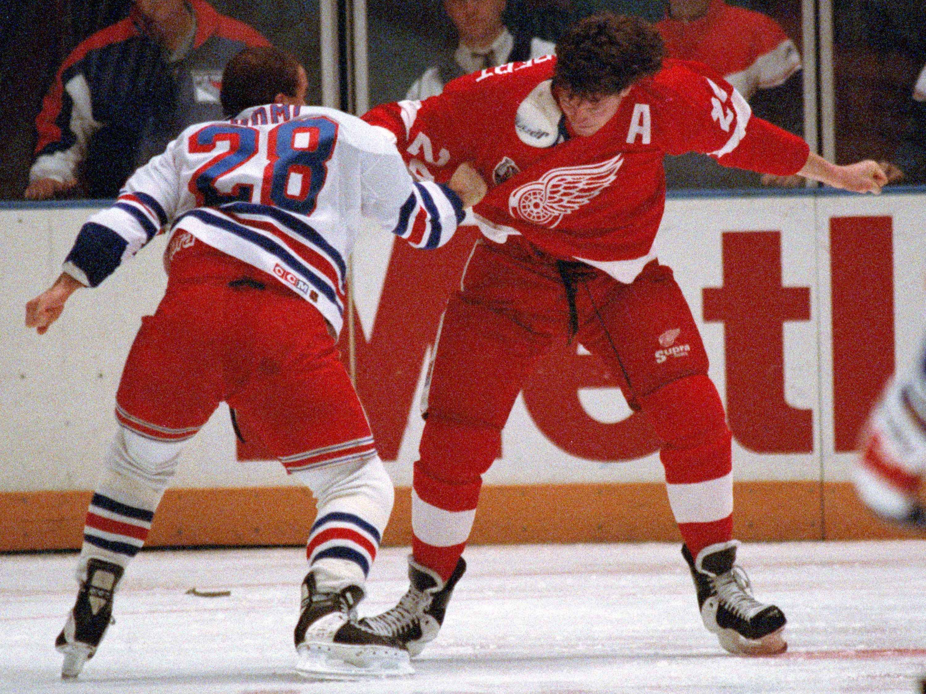 In this Dec. 2, 1992, file photo, the New York Rangers' Tie Domi (28) fights with Detroit Red Wings forward Bob Probert (24) less than a minute into the first period of a game at New York's Madison Square Garden.