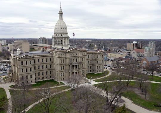 High above the Lansing skyline, and pedestrians far below, workers begin erecting scaffolding as part of a multi-million dollar renovation project on the dome atop the Michigan Capitol.