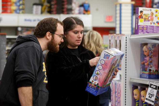"""Kevin Furlong, left, and his fiancé Samantha Bailey traveled from Jackson, Michigan to shop for Christmas presents at the Toys """"R"""" Us on Howard Avenue in Windsor, Ontario, Canada. Bailey and Furlong signed up to donate a gift through the Salvation Army's Angel Tree Christmas Program and were assigned to shop for a one-year-old girl."""