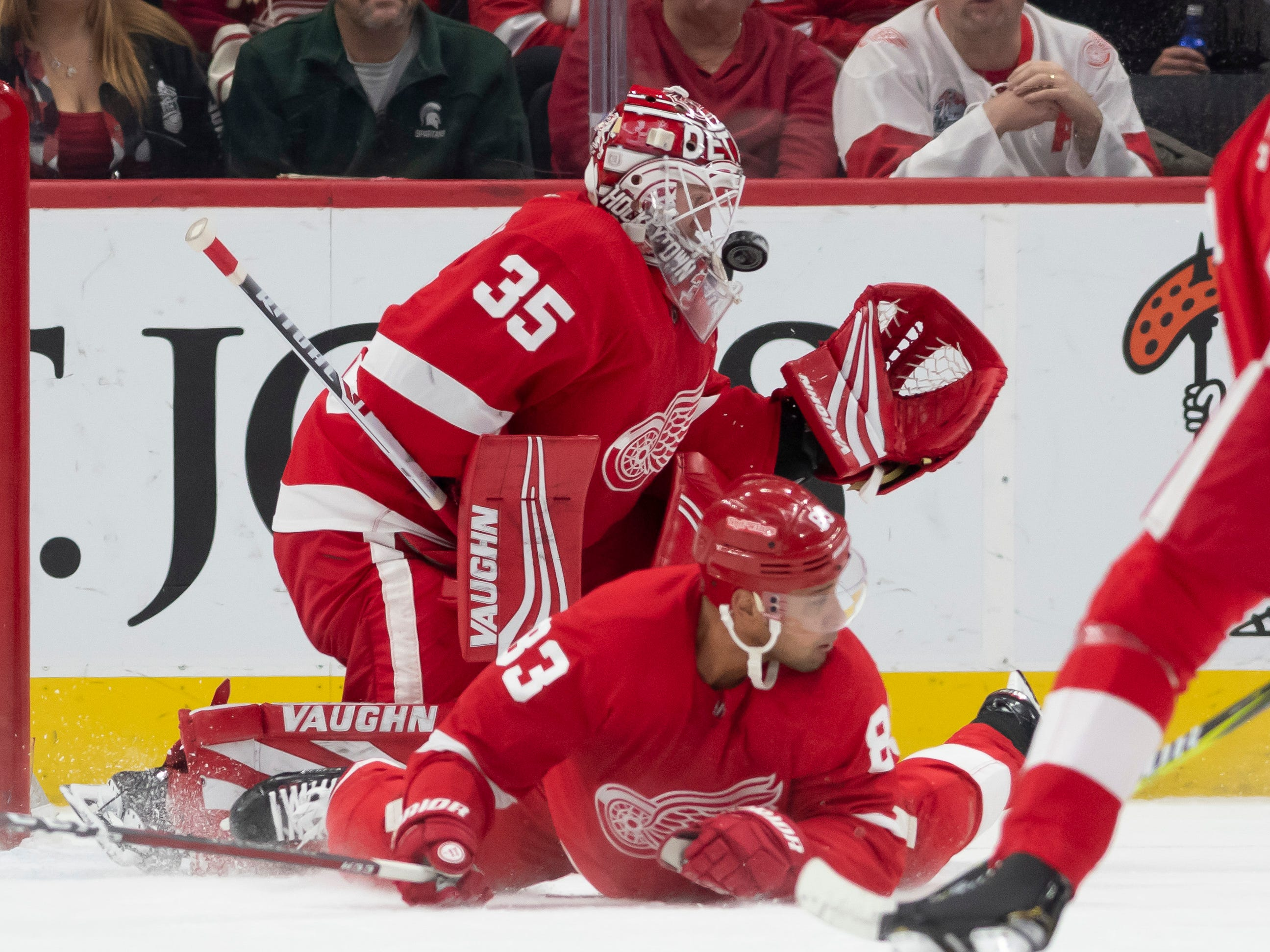 Detroit defenseman Trevor Daley tries to block a shot as goaltender Jimmy Howard stops the puck with his mask in the first period.