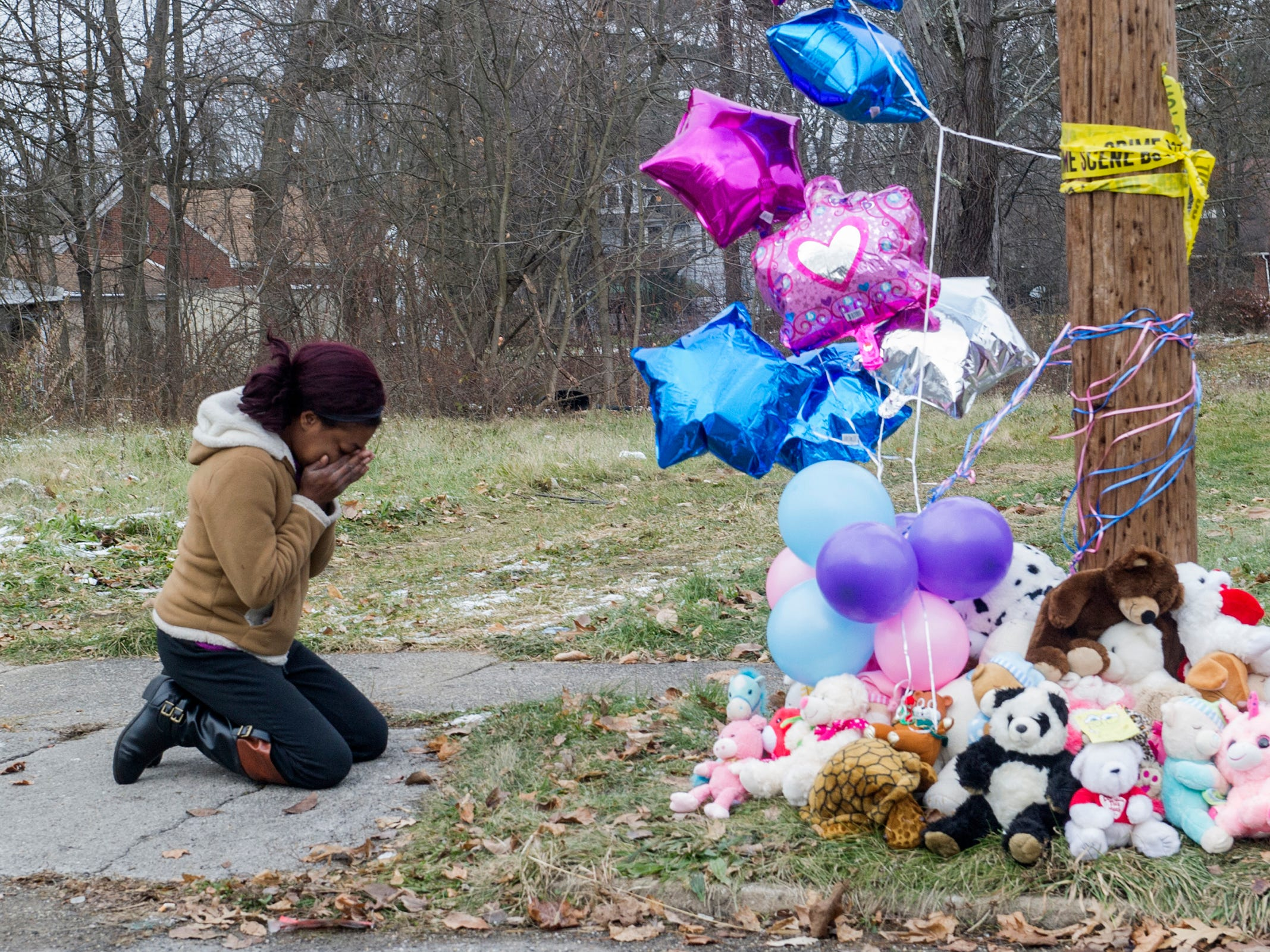 Chandriel Strong, 29, breaks down while paying respects at a deadly fire scene Monday, Dec. 10, 2018, in Youngstown, Ohio. The fire broke out on Sunday night killing 5 children, ages 9, 3, 2, and 1-year-old twins and injuring the mother who jumped out from the second-floor window.