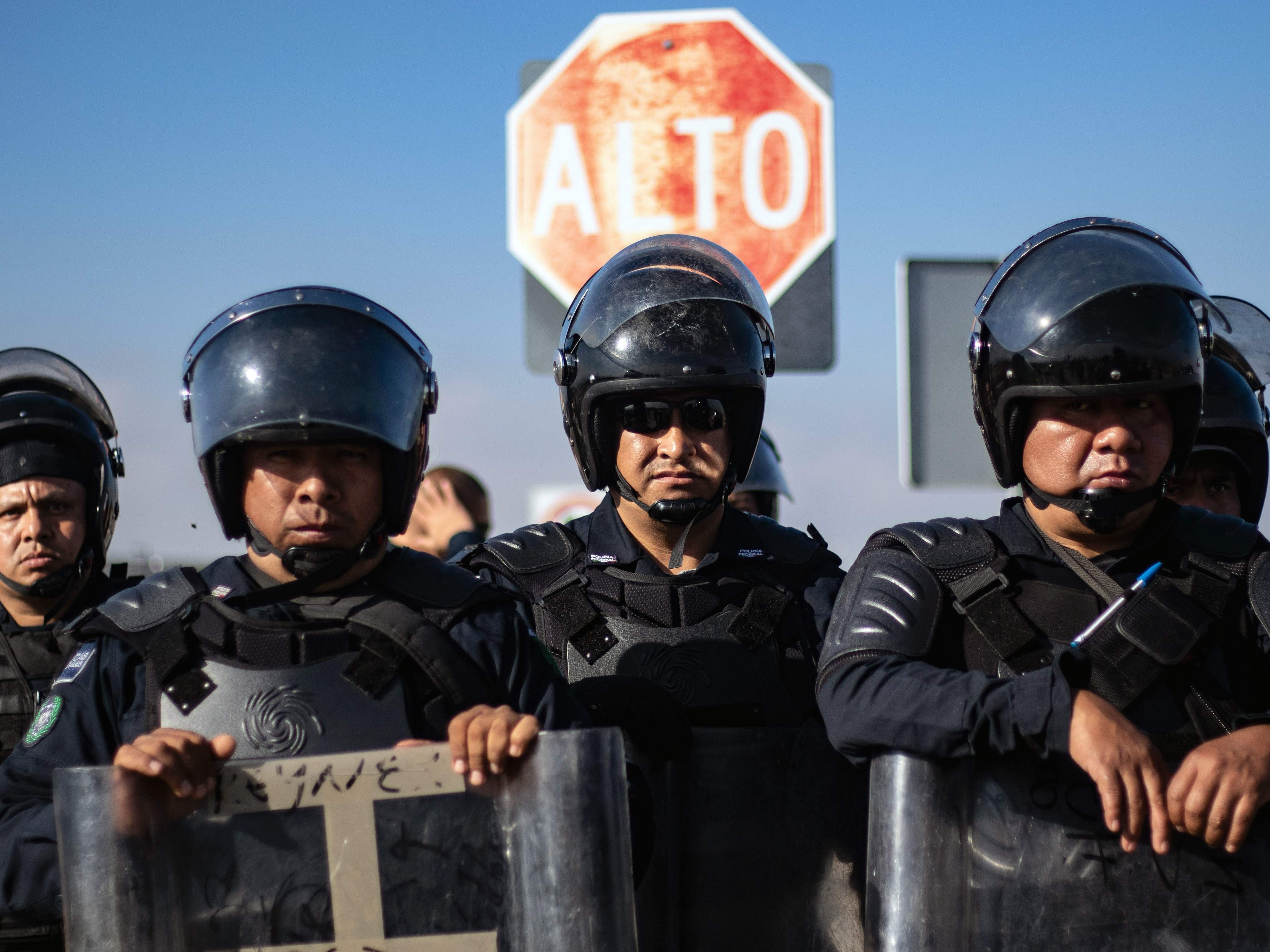 Federal Riot Police stand guard as a group of Central American migrants march to the U.S. Consulate to deliver a petition, in Tijuana, Baja California state, Mexico on December 11, 2018. - Thousands of Central American migrants, mostly Hondurans, have trekked for over a month in the hopes of reaching the United States.