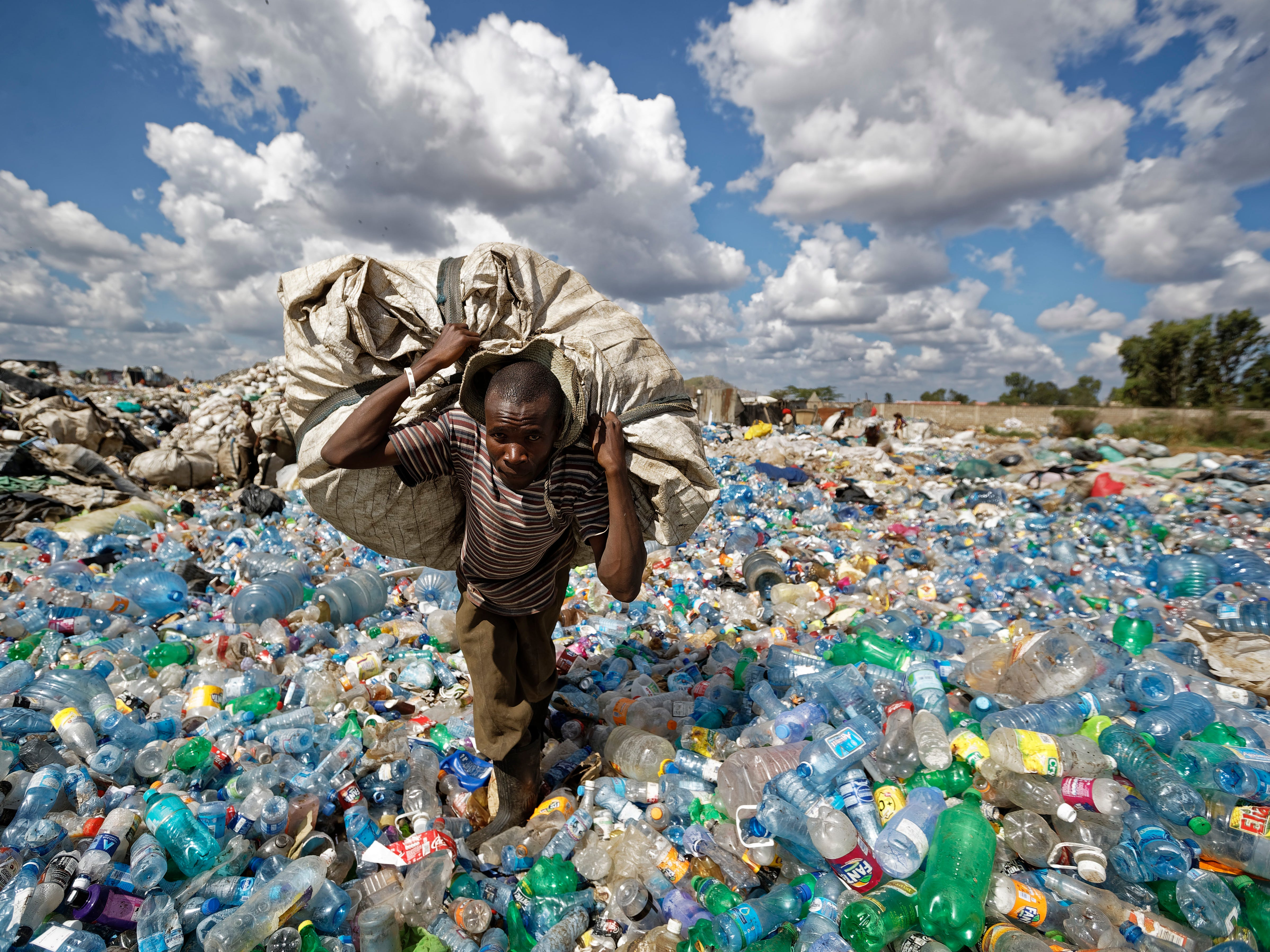 A man walks on a mountain of plastic bottles as he carries a sack of them to be sold for recycling Dec. 5, 2018, in the Dandora slum of Nairobi, Kenya.