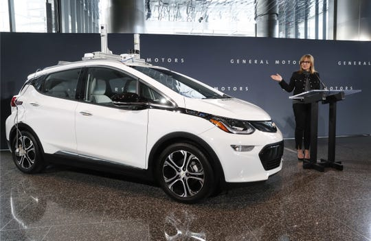 In this Dec. 15, 2016, file photo, General Motors Chairman and CEO Mary Barra speaks next to a autonomous Chevrolet Bolt electric car in Detroit.