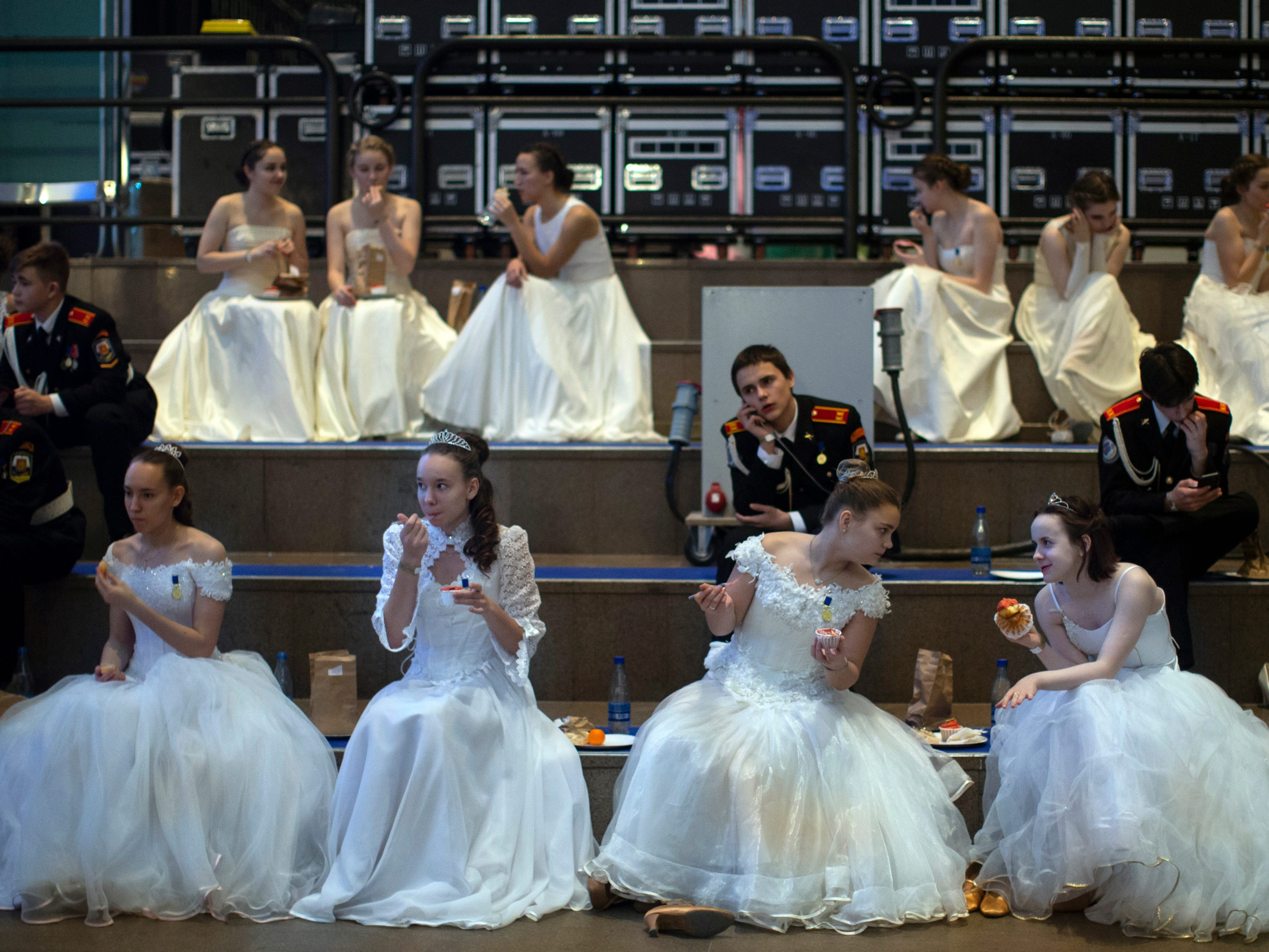Students sit backstage during an annual ball in Moscow, Russia, Tuesday, Dec. 11, 2018. In the revival of a czarist tradition, more than 1,000 students both from military and general schools travelled from all over Russia to Moscow to take part in the annual ball.