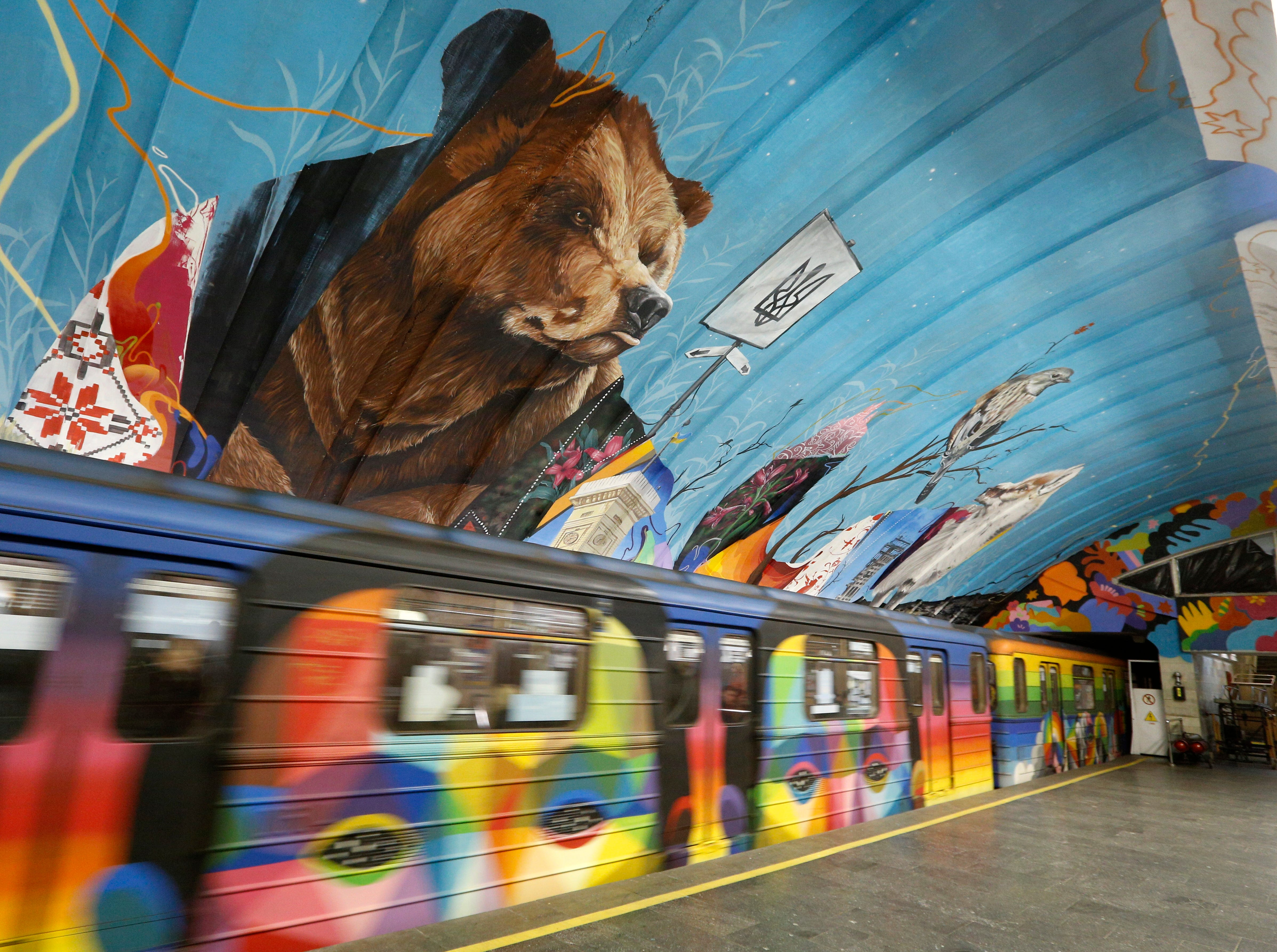 """A train passes by a mural depicting a bear in an underground metro station in Kiev, Ukraine, Tuesday, Dec. 11, 2018. Eight artists, including Apollo Tores from Brazil and Matthew Dawn from Belgium, have been performing an artist project called """"More Than Us"""" that reflects their personal concept on life in Ukraine."""