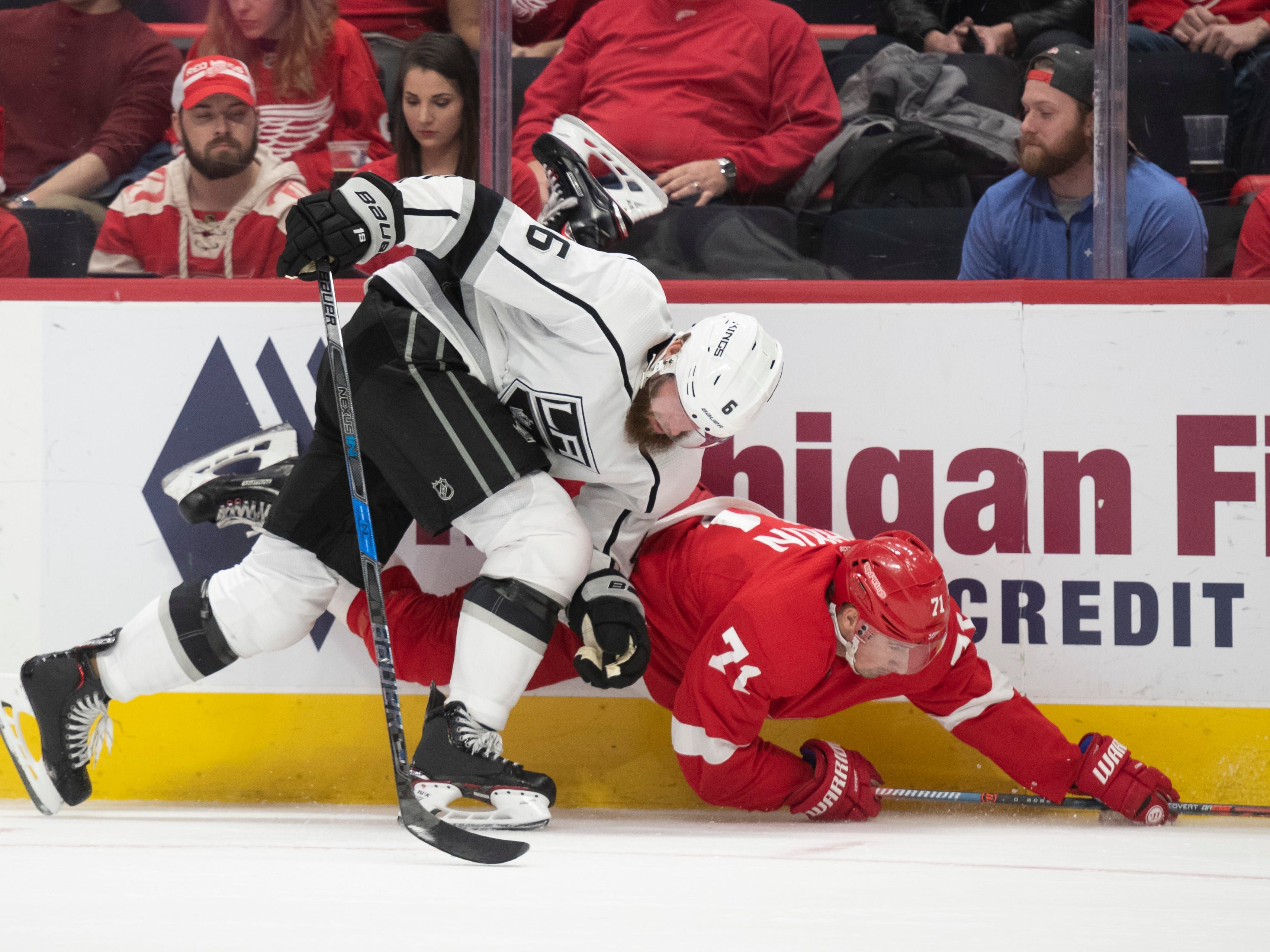 Detroit center Dylan Larkin and Los Angeles defenseman Jake Muzzin collide along the boards in the first period.