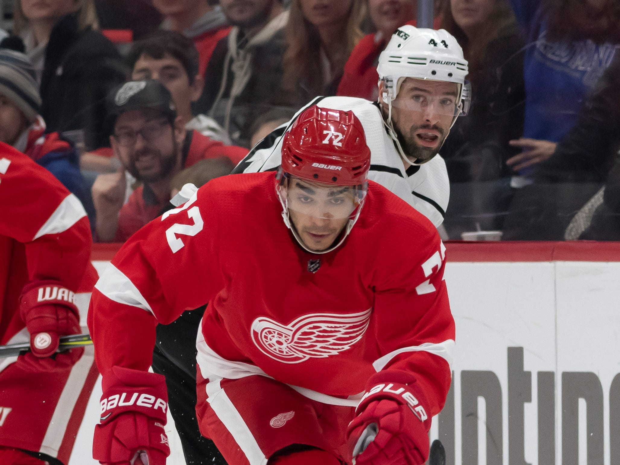 Detroit center Andreas Athanasiou moves the puck away from Los Angeles center Nate Thompson in the first period.