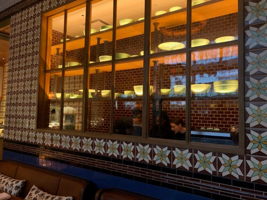 An area for servers can be seen from a smaller dining area, trimmed with elegant tile work.