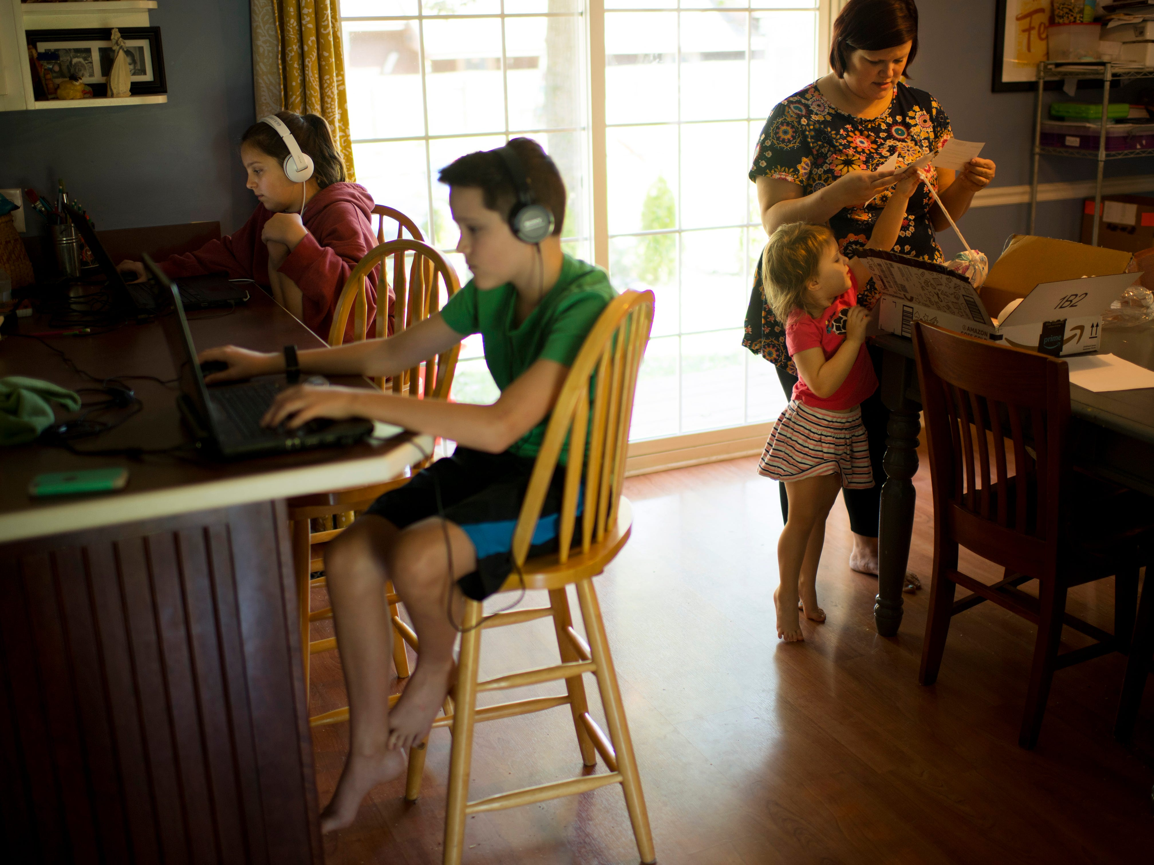 Heather Harper gets help from Jacinda, 3, with the mail as Penny, 11, and Truman, 12, take a break from homework in their Newburgh, Ind., home Sept. 5, 2018. The children are homeschooled. Lucy, 15, the oldest daughter, attends Signature School.
