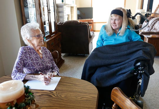 Ruth Burmeister of Fond du Lac helps Debbie Lunda write a letter Thursday, December 6, 2018 at Lunda's home in Fond du Lac, Wisconsin. Lunda was injured in a car crash in 2002 which left her without the use of her arms and legs. A care worker shortage has left the Lunda's with a lack of help. Doug Raflik/USA TODAY NETWORK-Wisconsin