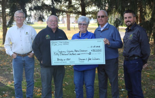 From left, Jim Fails, Brad Lawrence, Sharon Wilson, Joe Wilson, and Sandusky County Park District Director Andrew Brown display a check for $50,000 donated by the Wilsons to help build a bridge over Muddy Creek.