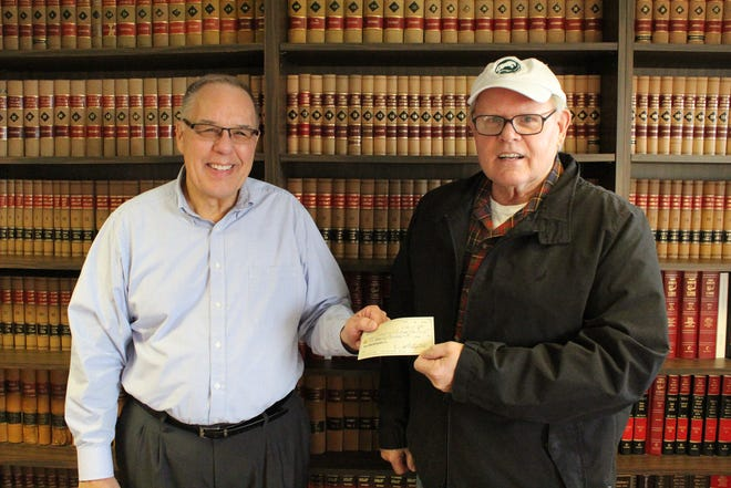 Gibsonburg Educational Foundation President Ladd Beck, left, and secretary Dan Henery hold a check for $500,000 donated by Henery's father Maurice, who left the money  to the foundation upon his death in July.